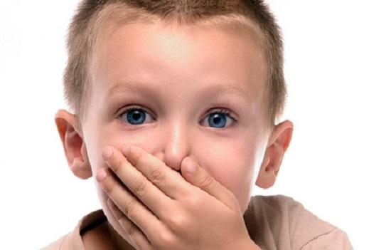 мальчик прикрывает рот ладонью