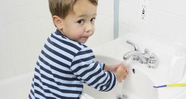 Мальчик моет руки, чтобы не заболеть инфекцией
