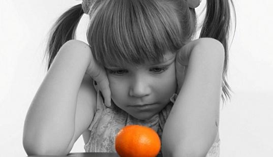 девочка не может съесть апельсин