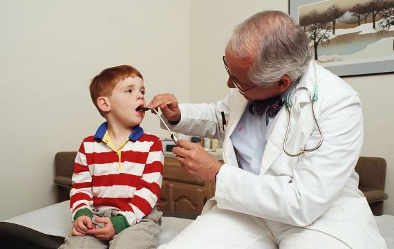 Врач осматривает мальчика на наличие ангины