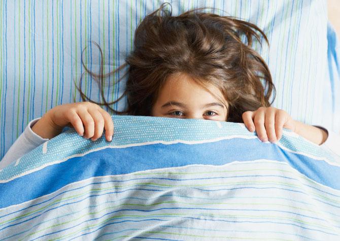 девочка прячется под одеялом