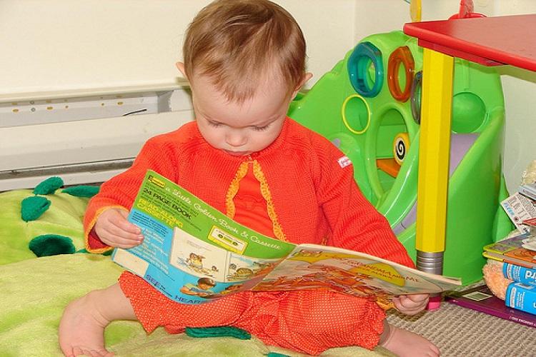 ребенок смотрит в книжку