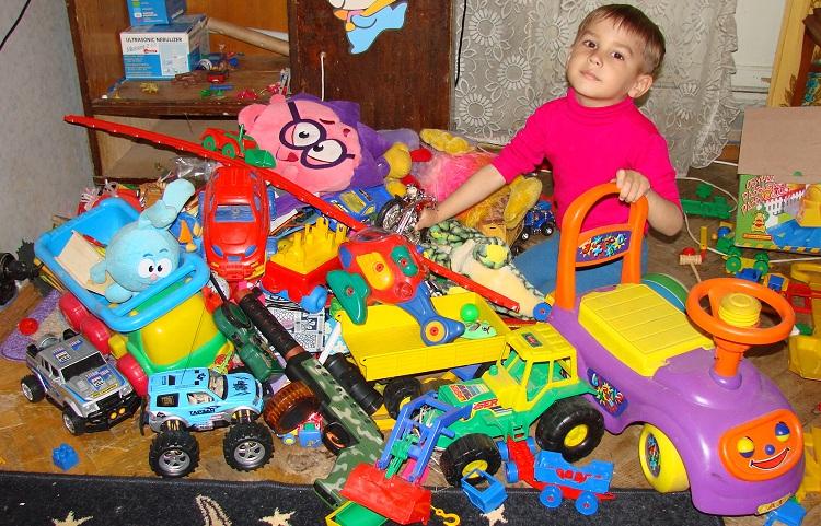 ребенок среди кучи игрушек