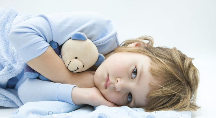 Грустный ребенок лежит на кровати