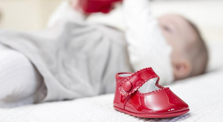 ребенок лежит и играет с обувью