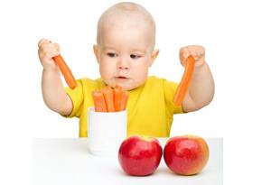 Ребенок укладывает морковь в чашку