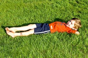 мальчик лежит на траве