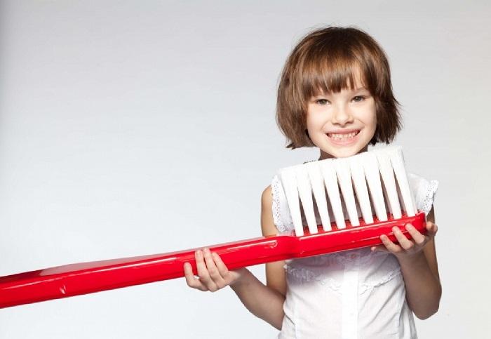 Ребенок с большой зубной щеткой