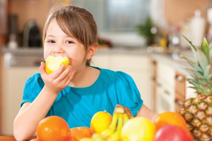 Девочка ест фрукты для поднятия иммунитета