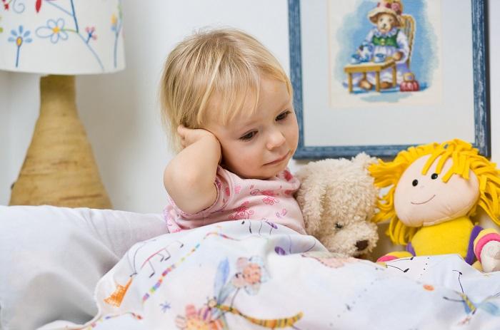 Девочка держится за голову в кровати