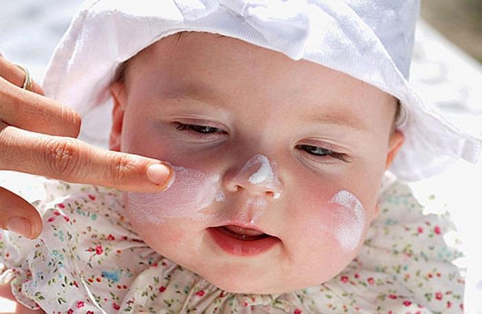 Младенец с защитным кремом от солнца на лице