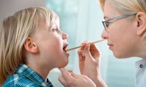Врач осматривает горло больного малыша