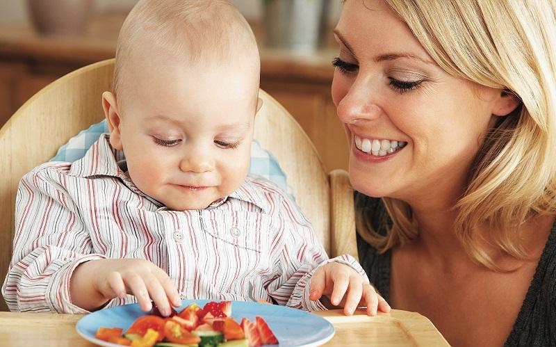 Мама смотрит, как малыш пробует есть сам