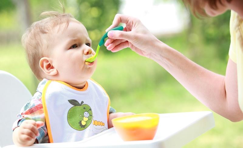 Мама кормит малыша пюре с ложечки