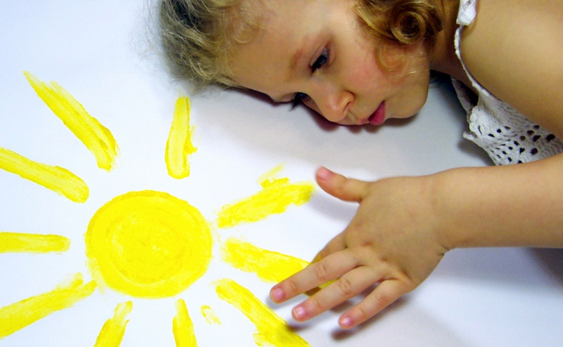 Девочка рисует солнышко руками