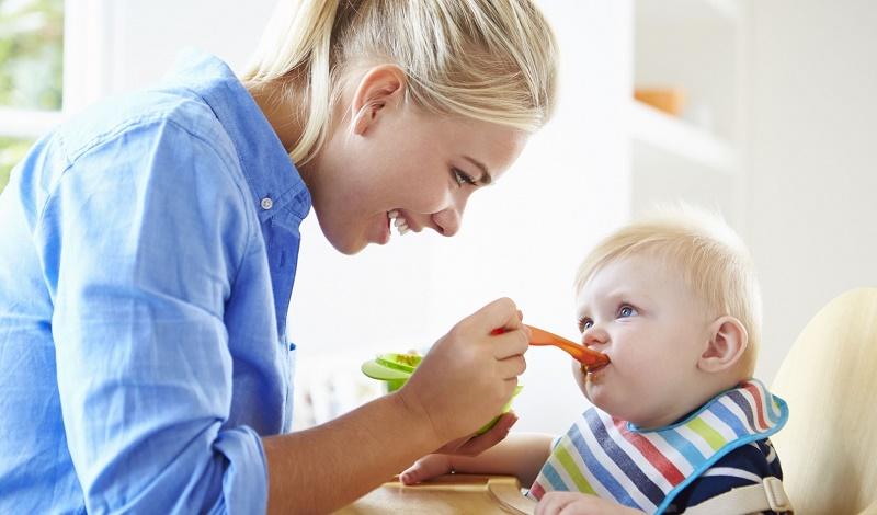 Мама кормит своего малыша кашей