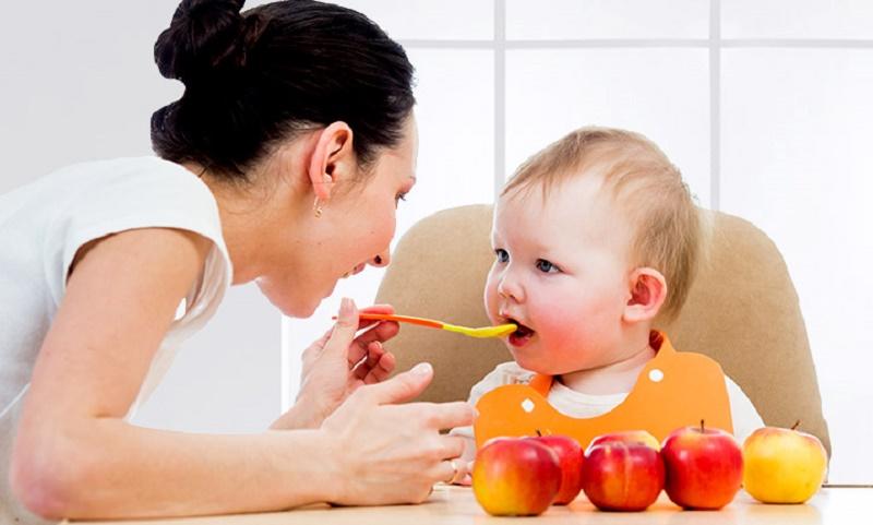 Мама кормит малыша с ложечки фруктовым пюре