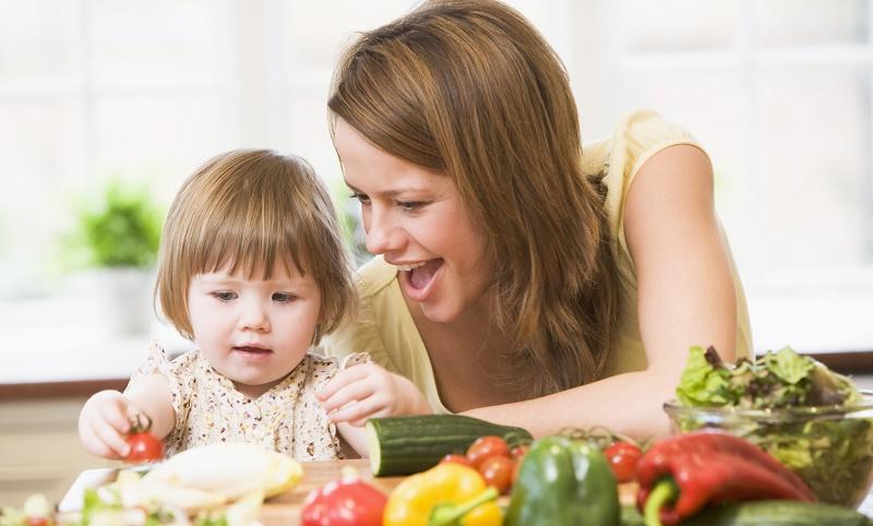 Мама с дочкой готовят овощной салат
