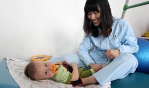 Мама делает массаже ребенку, больному ДЦП