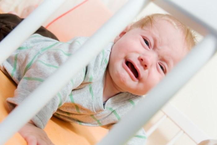 Грудной ребенок плачет в кроватке