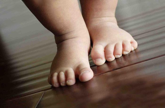 Здоровые ножки ребенка идут по полу
