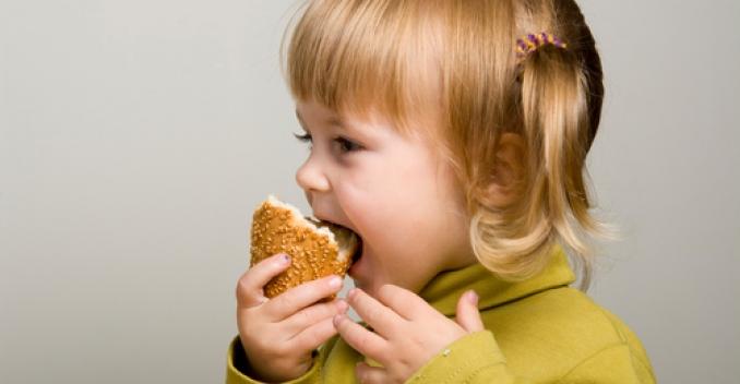 Девочка ест фастфуд